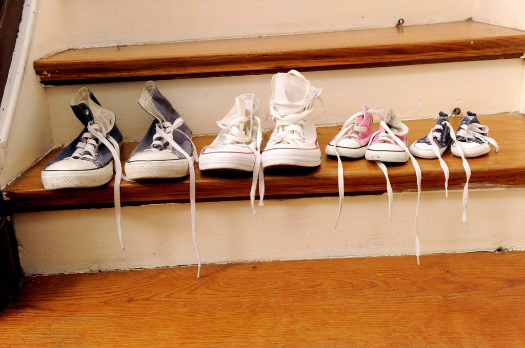 Stock Photo: 1848-570122 Sport shoes of a family with two children, lined up on a stair