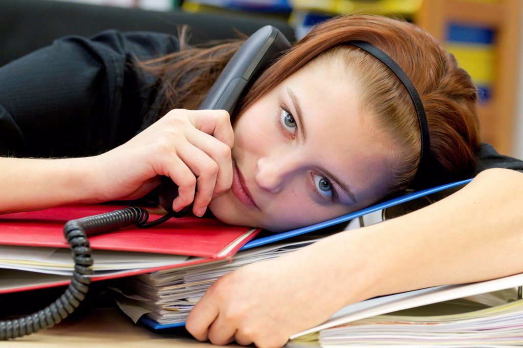 Stock Photo: 1848-571035 Exhausted office worker with telephone handset resting head on files and folders