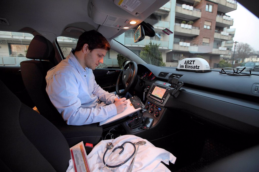 Young GP, general practitioner taking notes in his car after a home visit, car displaying the sign ´´Arzt im Einsatz´´, German for´´doctor on call´´, Essen, North Rhine_Westphalia, Germany, Europe : Stock Photo