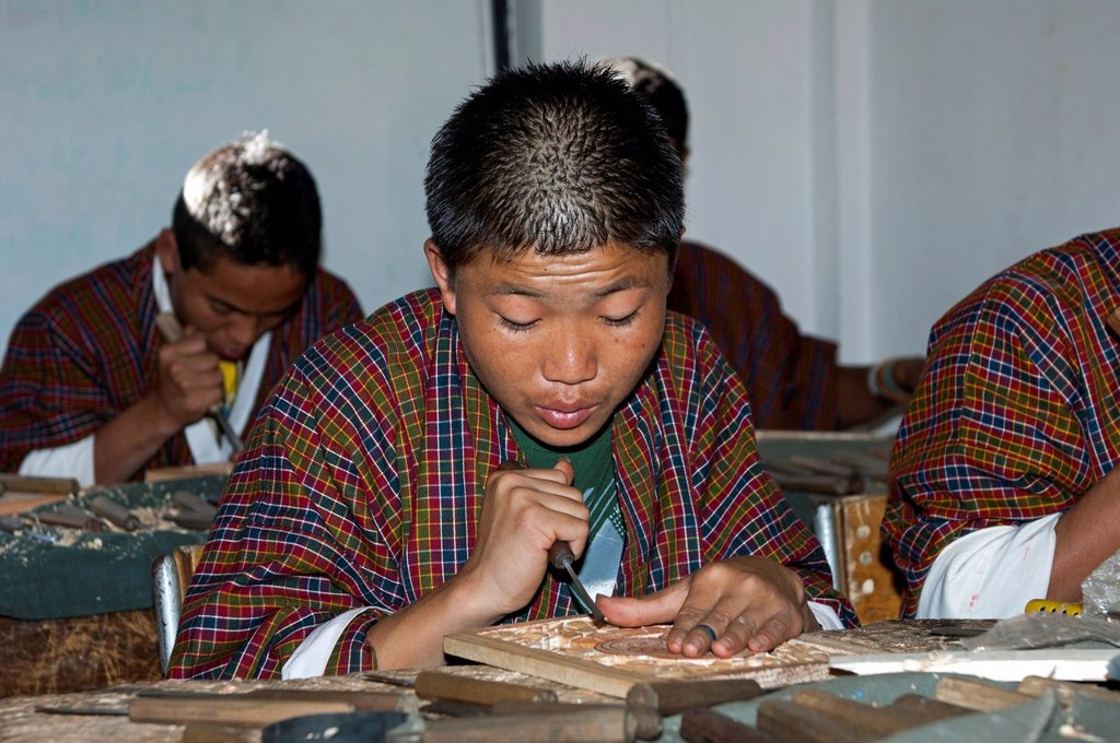 Stock Photo: 1848-571788 Highly concentrated students doing an apprenticeship in woodcarving at the National Institute of Traditional Arts and Crafts, Zorig Chusum, Thimphu, Bhutan, Asia