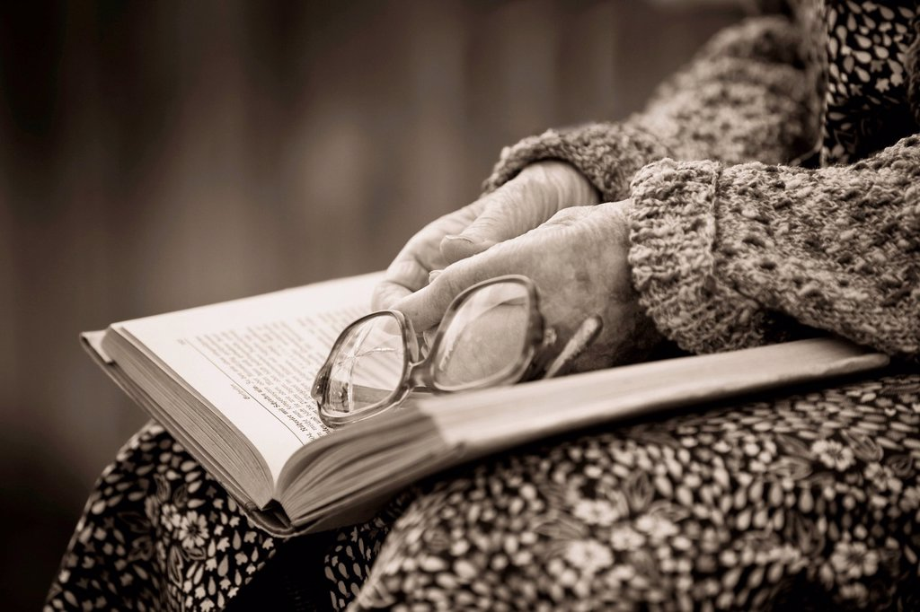 Hands of an old woman holding old broken glasses on a book, sepia processing : Stock Photo
