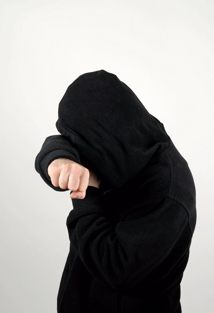 Stock Photo: 1848-573401 Young man wearing a black hooded shirt holding his arm protectively over his eyes obscuring his face