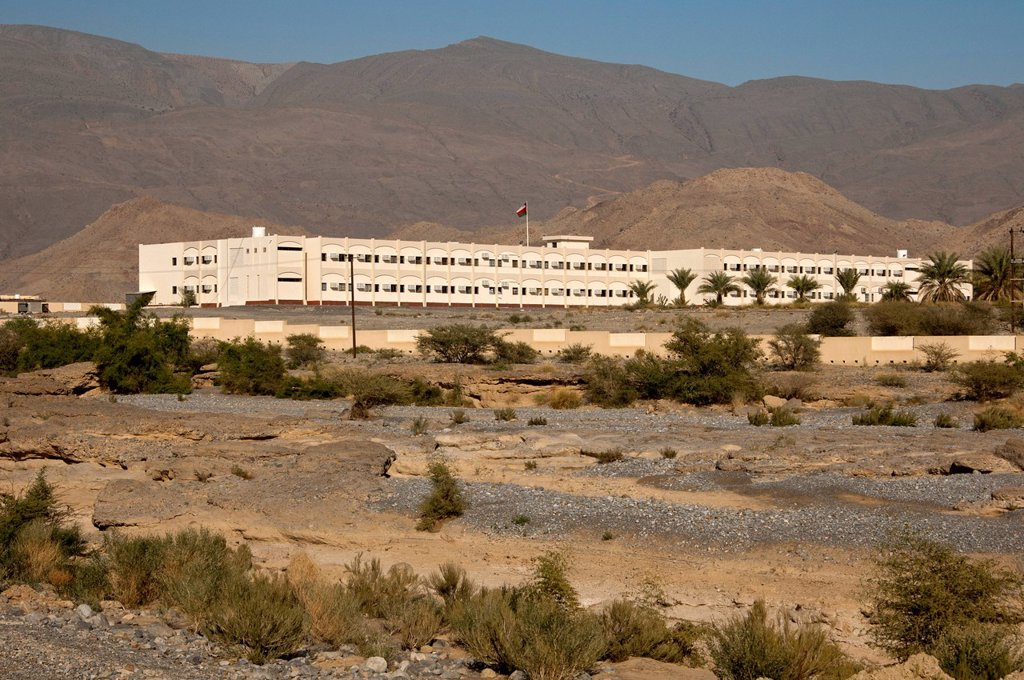 Modern school buildings in the barren landscape at the foot of the Hajar Mountains on the outskirts of Nizwa, Sultanate of Oman, Middle East, Asia : Stock Photo