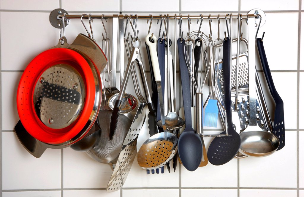 Various kitchen tools and utensils, hanging on a wall in a kitchen : Stock Photo