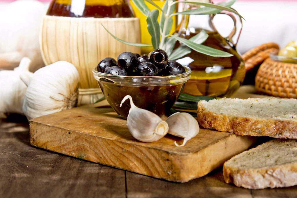 Olives, garlic, olive oil and fresh bread on a wooden table : Stock Photo