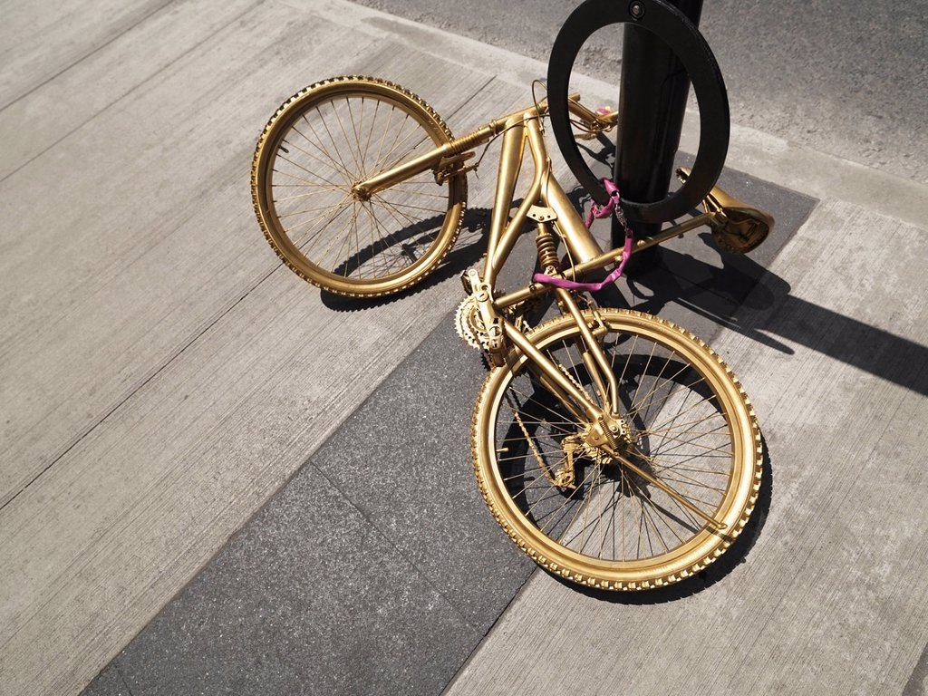 Bicycle painted gold, chained to a post : Stock Photo