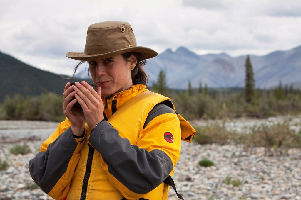 Young woman drinking, enjoying a cup of tea, Wind River, Peel Watershed, Northern Mackenzie Mountains behind, Yukon Territory, Canada : Stock Photo