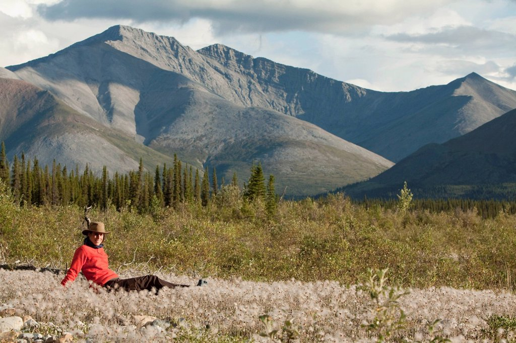 Stock Photo: 1848-579352 Young woman relaxing, enjoying evening light, sitting in the grass, Cotton Grass, Peel Watershed, Northern Mackenzie Mountains behind, Wind River, Yukon Territory, Canada