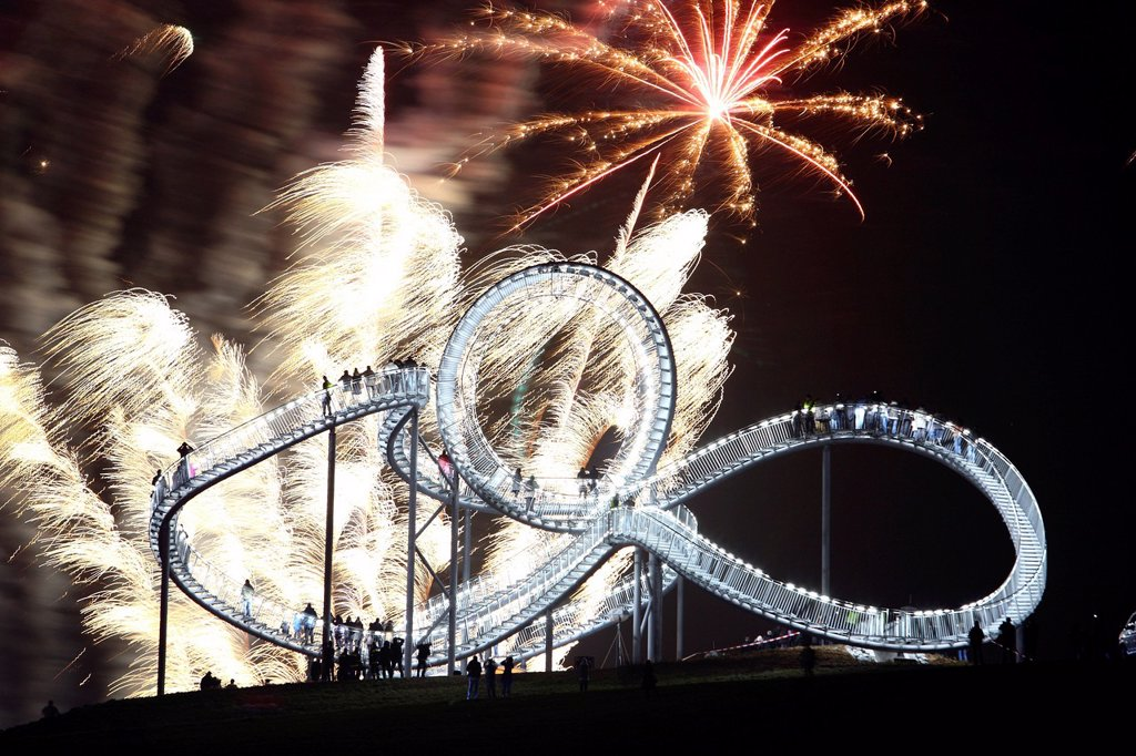 Fireworks display during opening of the walkable landmark sculpture in the shape of a roller coaster, ´´Tiger & Turtle – Magic Mountain´´ by Heike Mutter and Ulrich Genth, Angerpark on Heinrich_Hildebrand_Hoehe, mining waste tip, Duisburg, North Rhine_Wes. Fireworks display during opening of the walkable landmark sculpture in the shape of a roller coaster, ´´Tiger & Turtle – Magic Mountain´´ by Heike Mutter and Ulrich Genth, Angerpark on Heinrich_Hildebrand_Hoehe, mining waste tip, Duisburg, Nor : Stock Photo