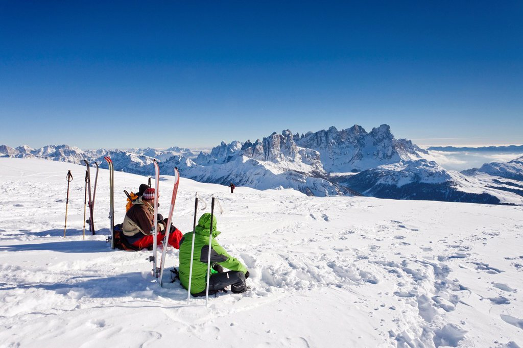 Stock Photo: 1848-581202 Ski tourers taking a break on the summit of Mt Uribrutto, above Passo Valles, Dolomites, Pale di San Martino mountains and the Passo Rolle in the back, Trentino, Italy, Europe