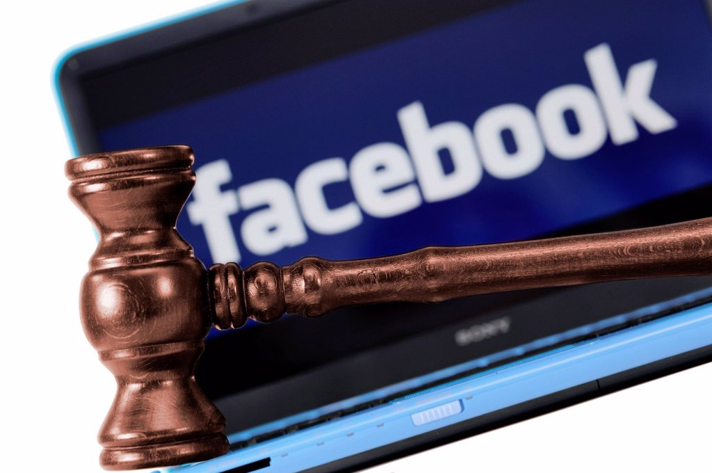 Stock Photo: 1848-582374 A judge´s gavel in front of a laptop computer with a Facebook logo on the monitor