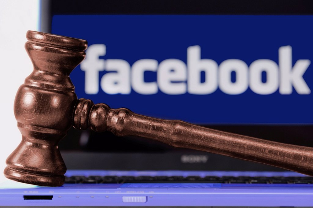 A judge´s gavel in front of a laptop computer with a Facebook logo on the monitor : Stock Photo