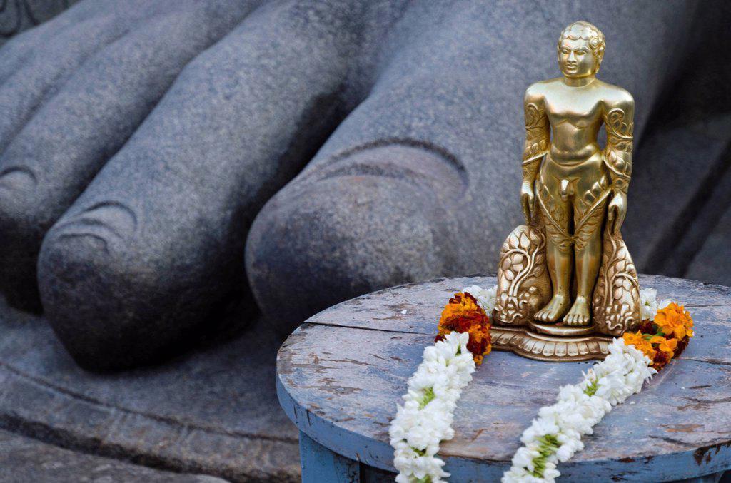 The small statue of Bahubali at the feet of the gigantic staue of Gomateshwara in Sravanabelagola, used for special rituals, Karnataka, India, Asia : Stock Photo