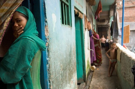 Stock Photo: 1848-58346 Although the predominantly Muslim slum dwellers are relatively open and approachable, this girl feels embarrassed about being photographed and tries to hide her face behind her hand in a multi_story residential building in the slums of Pilkana. Howrah, Ho