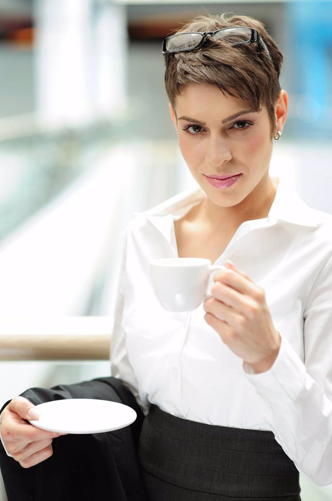 Young businesswoman holding a cup of coffee : Stock Photo