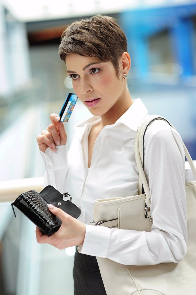 Young businesswoman taking her credit card out of her wallet : Stock Photo