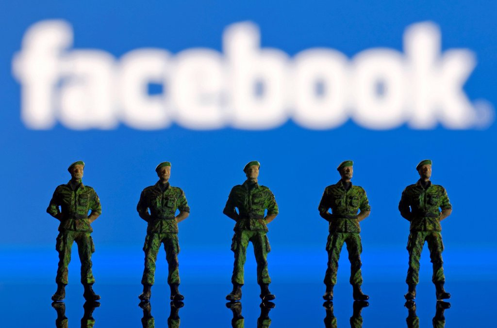 Stock Photo: 1848-583618 A row of soldiers, miniature figures standing in front of a blurred Facebook logo, symbolic image