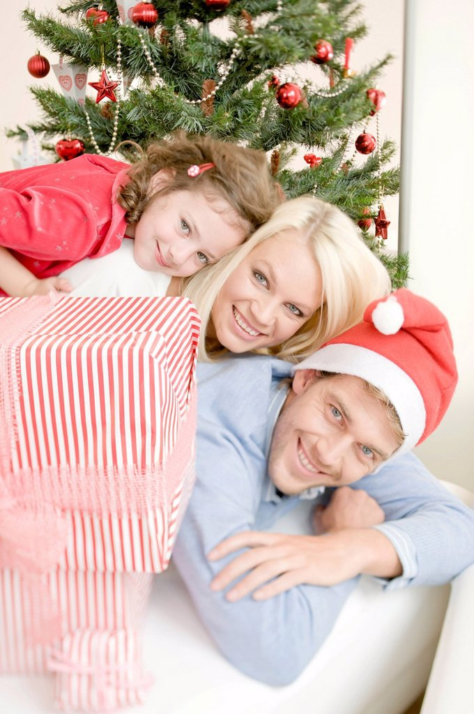 Young family next to Christmas presents in front of a Christmas tree : Stock Photo