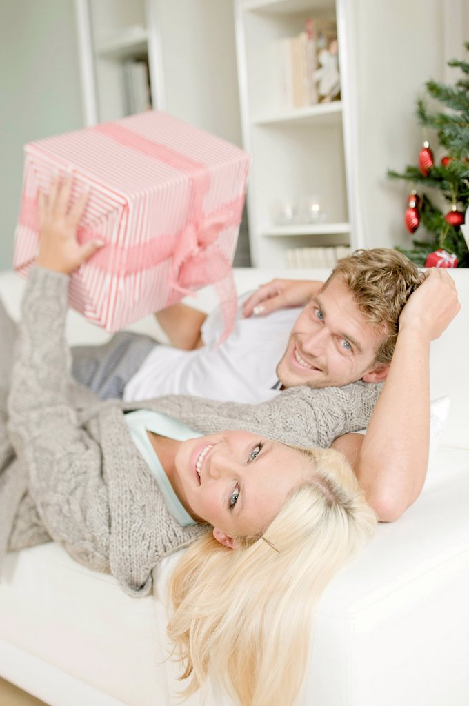 Young couple with a Christmas present lying on a sofa : Stock Photo