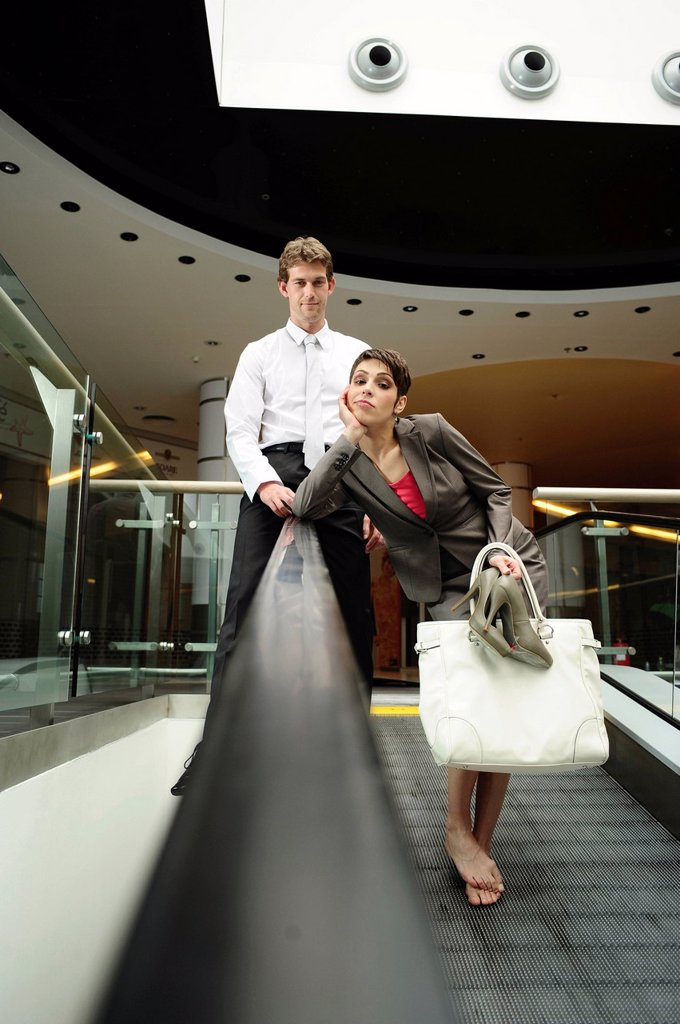 Stock Photo: 1848-584523 A young businesswoman and a young businessman posing on an escalator