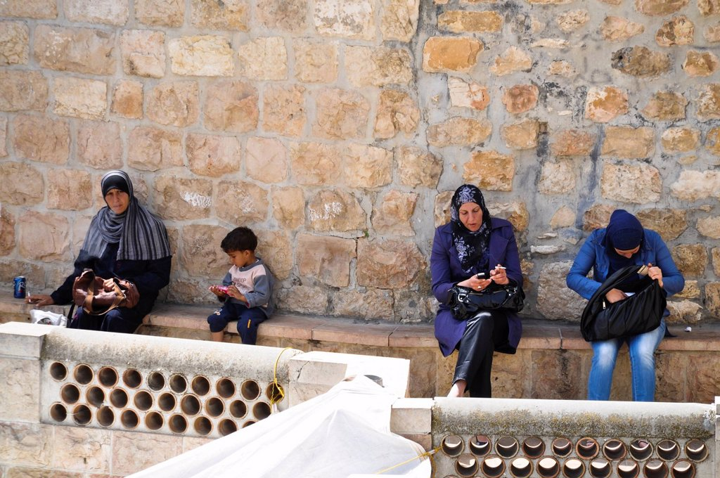 Veiled women smoking cigarettes and cell phones and a boy sitting on the city wall, Jerusalem, Israel, Middle East, Southwest Asia : Stock Photo