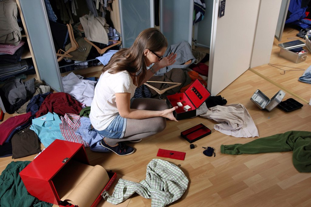 Young woman discovering the scene of a burglary, ransacked closet, jewellery box cleared out, cash box forced open, documents sought through : Stock Photo