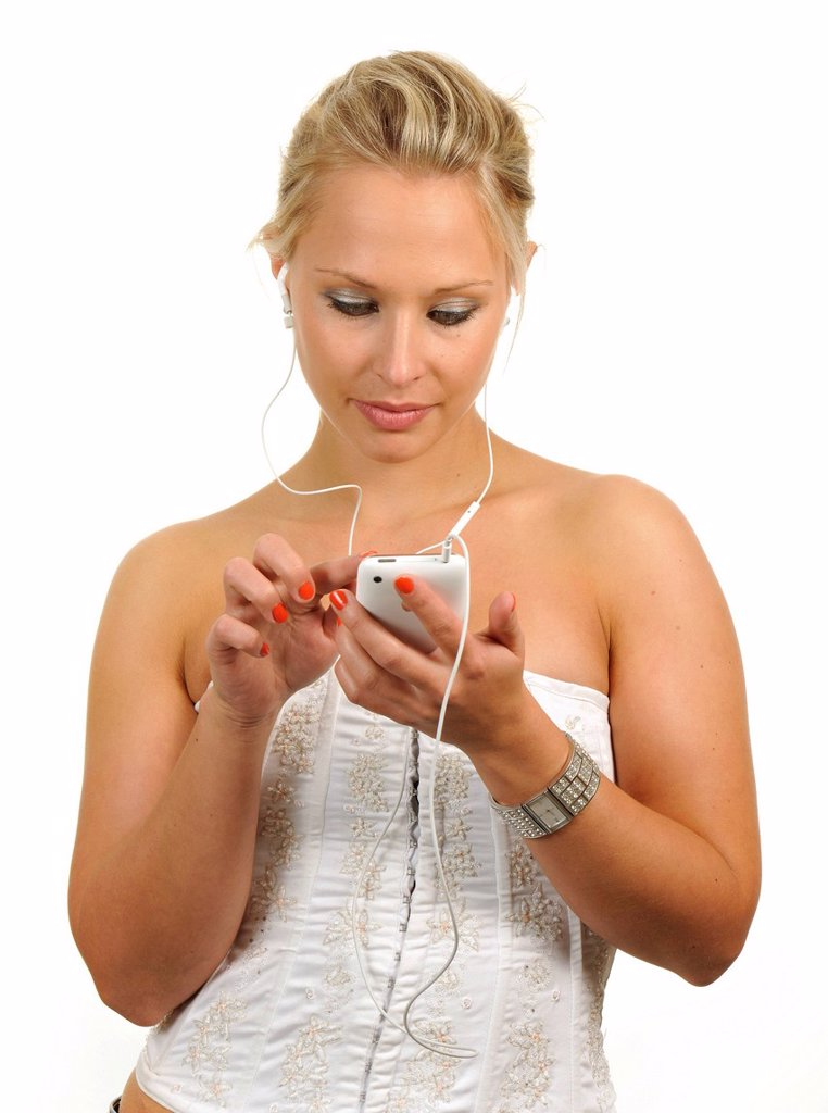 Stock Photo: 1848-586607 Young woman using a white Apple iPhone, listening to music with earphones