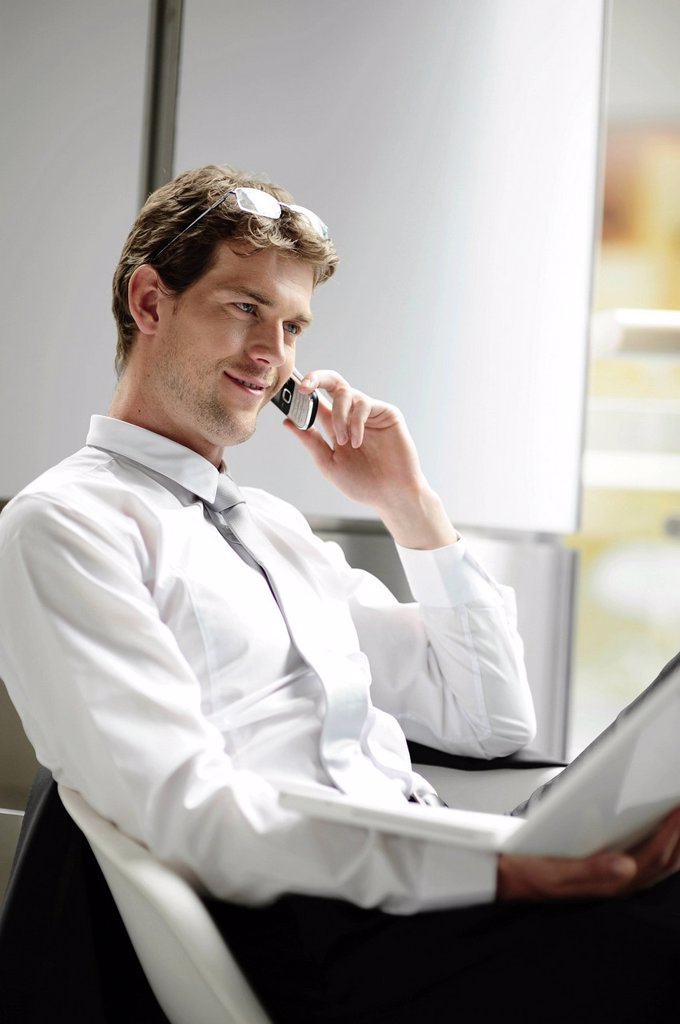 Stock Photo: 1848-587654 Young businessman with a laptop speaking on a mobile phone