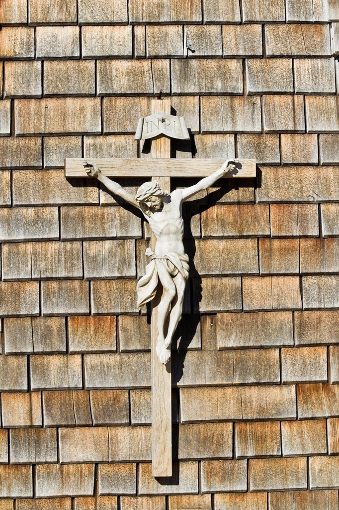 Crucifix, wooden cross on a wall with wooden shingles : Stock Photo