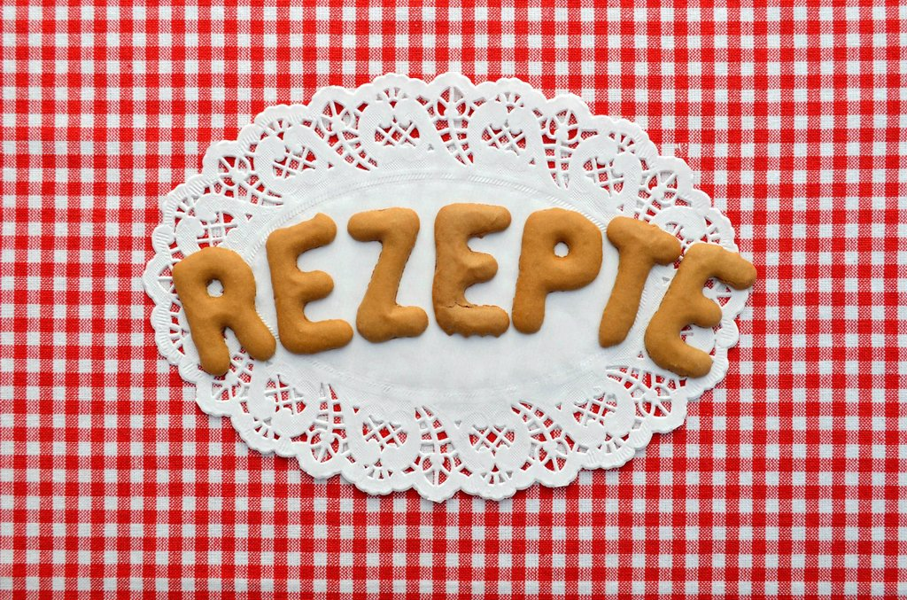 Rezept or recipe written in alphabet biscuits on paper doily : Stock Photo