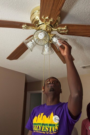 Stock Photo: 1848-59000 Volunteer from Xavier University replaces incandescent light bulbs in a home with energy_saving compact fluorescent bulbs, Bridge City, Louisiana, USA
