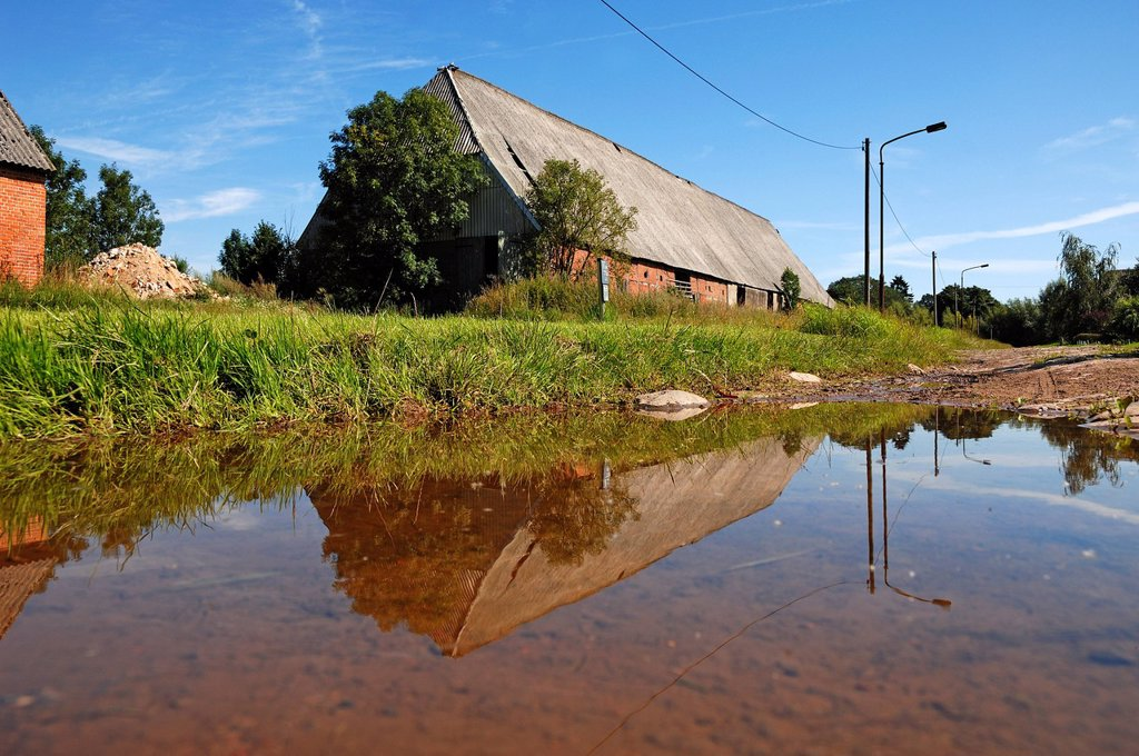 Old barn built in 1920 with reflection in a puddle, Gut Othenstorf estate, Othenstorf, Mecklenburg_Western Pomerania, Germany, Europe : Stock Photo