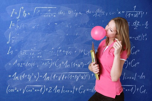 Schoolgirl blowing a bubble with bubble gum in front of a school blackboard with arithmetic problems : Stock Photo