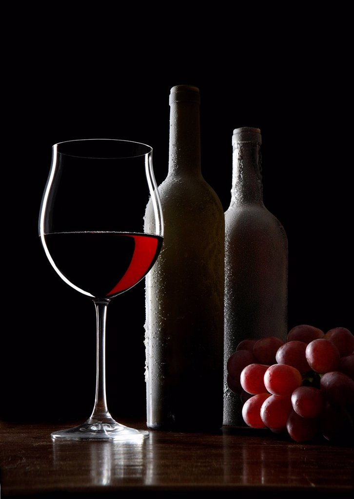 Red wine glass, wine bottles, grapes : Stock Photo
