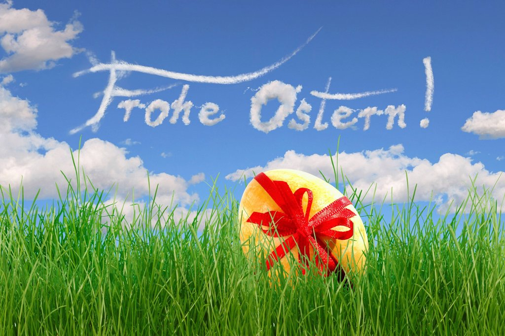Stock Photo: 1848-592707 Easter egg with a bow lying in the grass, lettering ´´Frohe Ostern´´, German for ´´Happy Easter´´