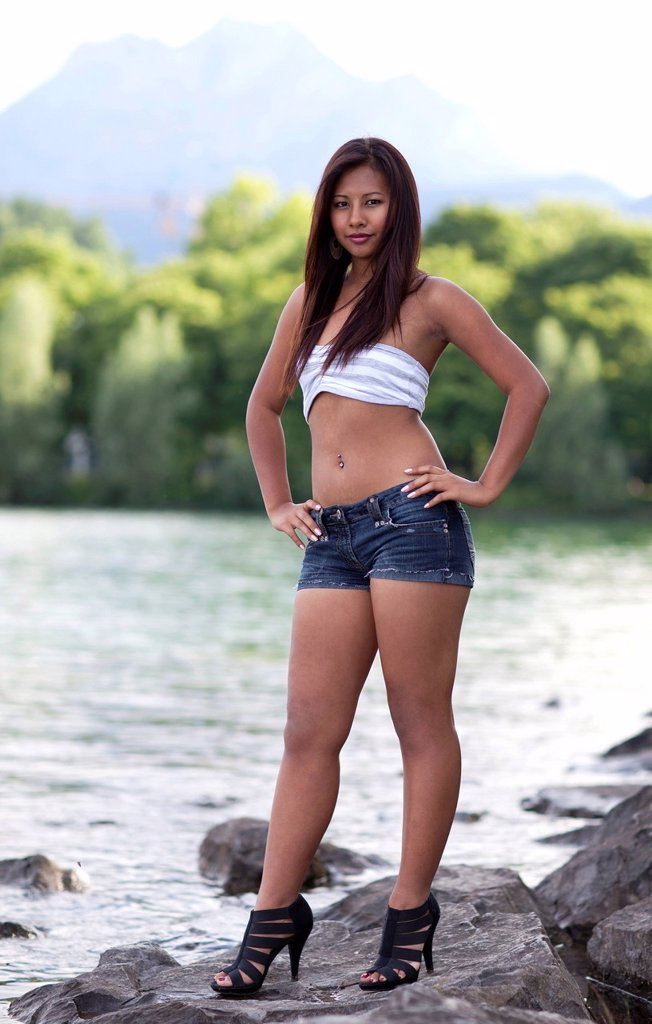 Stock Photo: 1848-594037 Young Asian woman, bare midriff, in hot pants and high heels, posing confidently on a rock on the shore of a lake