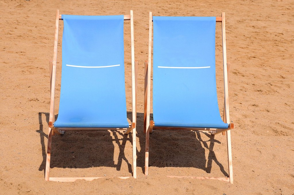 Two blue wooden deckchairs on the beach : Stock Photo