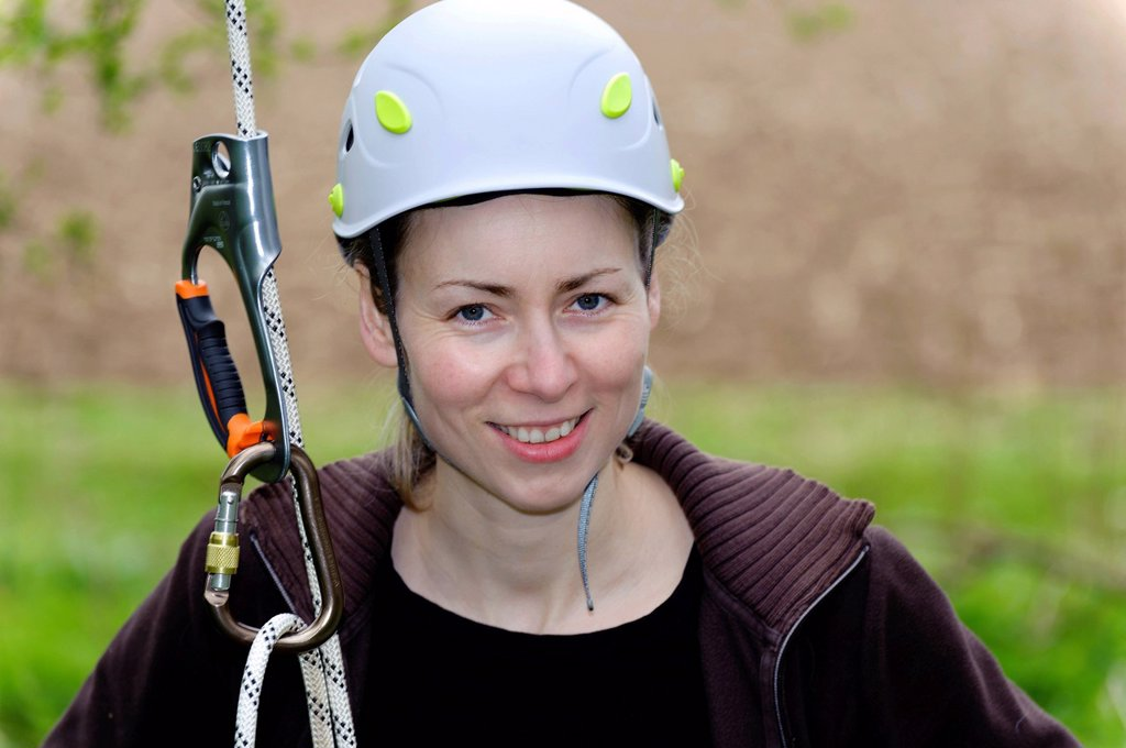 Young woman with a climbing rope wearing a safety helmet : Stock Photo