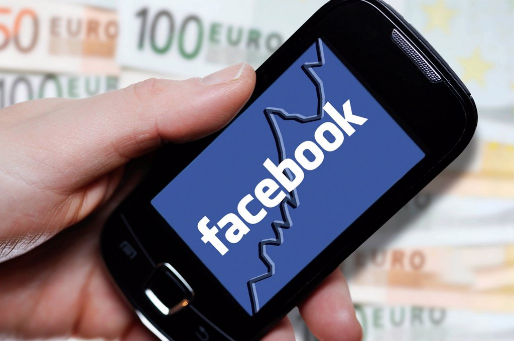 Stock Photo: 1848-598423 Hand holding a smartphone with a Facebook logo in front of euro notes, symbolic image for the Facebook IPO