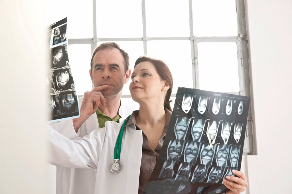 A male and a female doctor checking X_rays together : Stock Photo