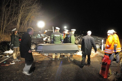 Victim of a heavy traffic accident is carried away from the accident scene by the undertakers in a casket, Gomadingen, Reutlingen Region, Baden_Wuerttemberg, Germany, Europe : Stock Photo