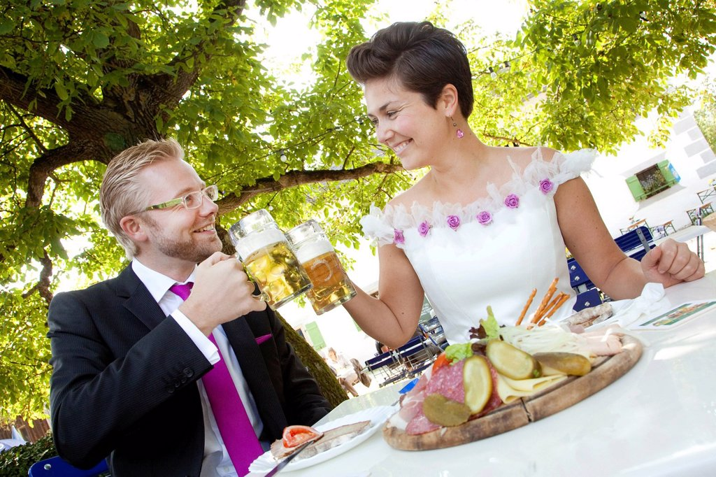 Bridal couple having a light meal and drinking beer in a Bavarian beer garden, Regensburg, Bavaria, Germany, Europe : Stock Photo
