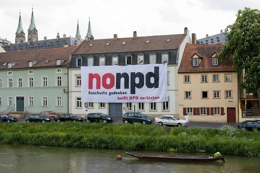 Facade of houses along Regnitz River with a placard protesting against the federal party convent of the National Democratic Party of Germany or NPD, 24.05.2008 _ 25.05.08, towers of the cathedral at back, Bamberg, Upper Franconia, Bavaria, Germany, Europe : Stock Photo