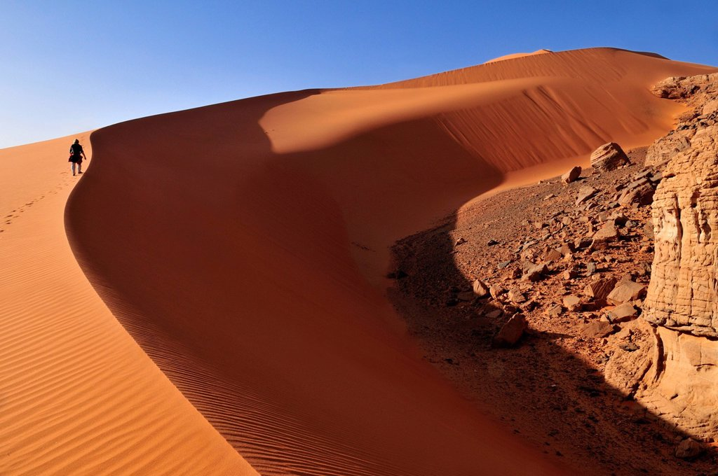 Woman climbing a sanddune at Tin Merzouga, Acacus Mountains or Tadrart Acacus range, Tassili n´Ajjer National Park, Unesco World Heritage Site, Algeria, Sahara, North Africa : Stock Photo