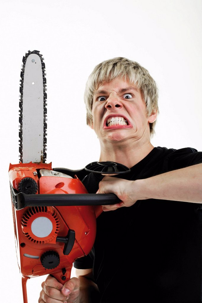 Young man with angry expression handling a chainsaw : Stock Photo