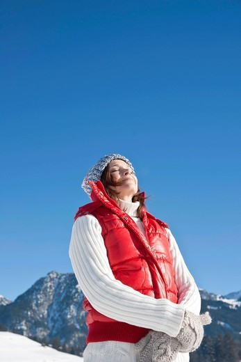 Woman standing in the snow enjoying the sunshine : Stock Photo