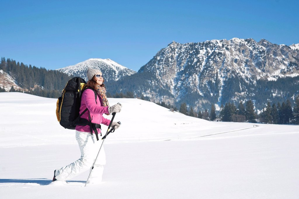 Woman hiking in the snow in the mountains : Stock Photo