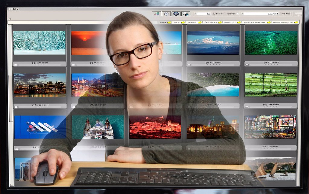 Young woman sitting at a computer, viewing her photo collection with photo editing software, view from within the computer, symbolic image : Stock Photo