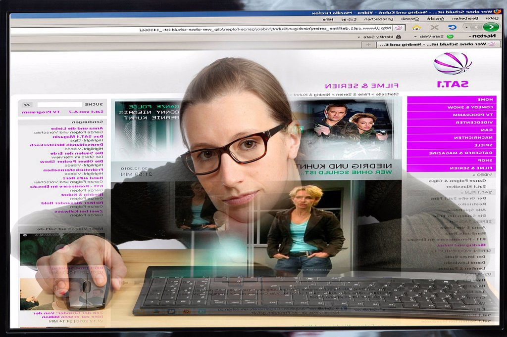 Young woman sitting at a computer surfing the Internet, viewing a page of the TV channel SAT1, watching a TV series on the internet, view from within the computer, symbolic image : Stock Photo