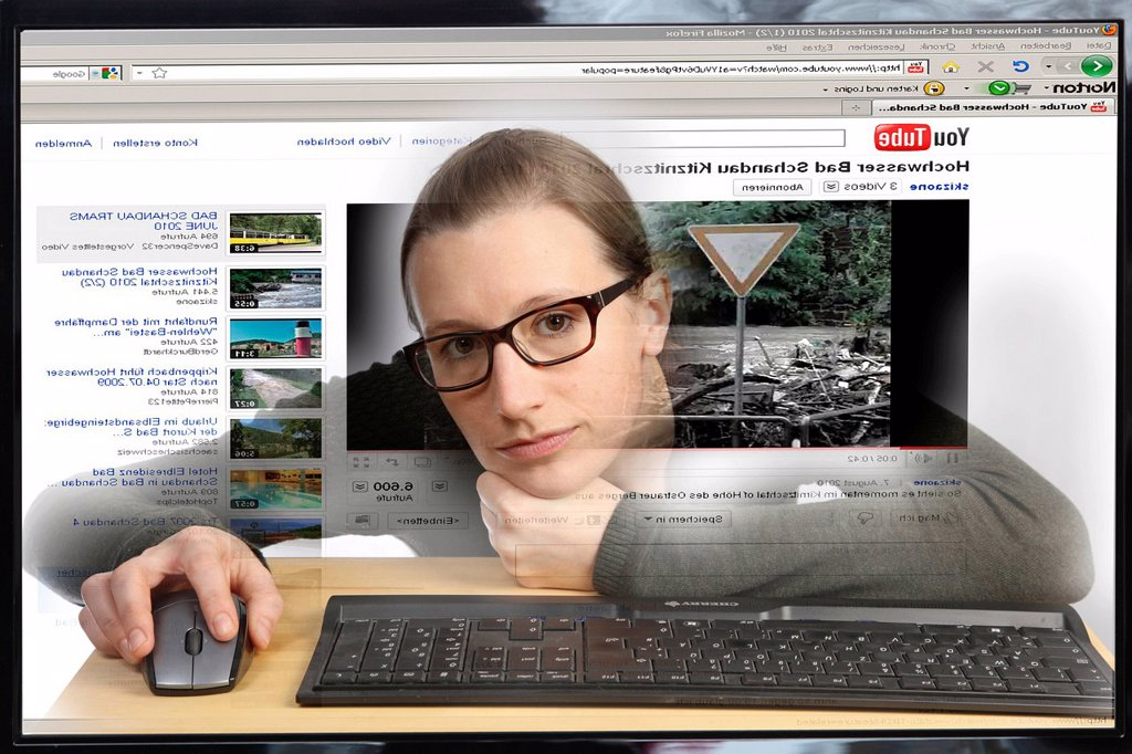 Young woman sitting at a computer surfing the Internet, viewing a video on the YouTube site, view from within the computer, symbolic image : Stock Photo